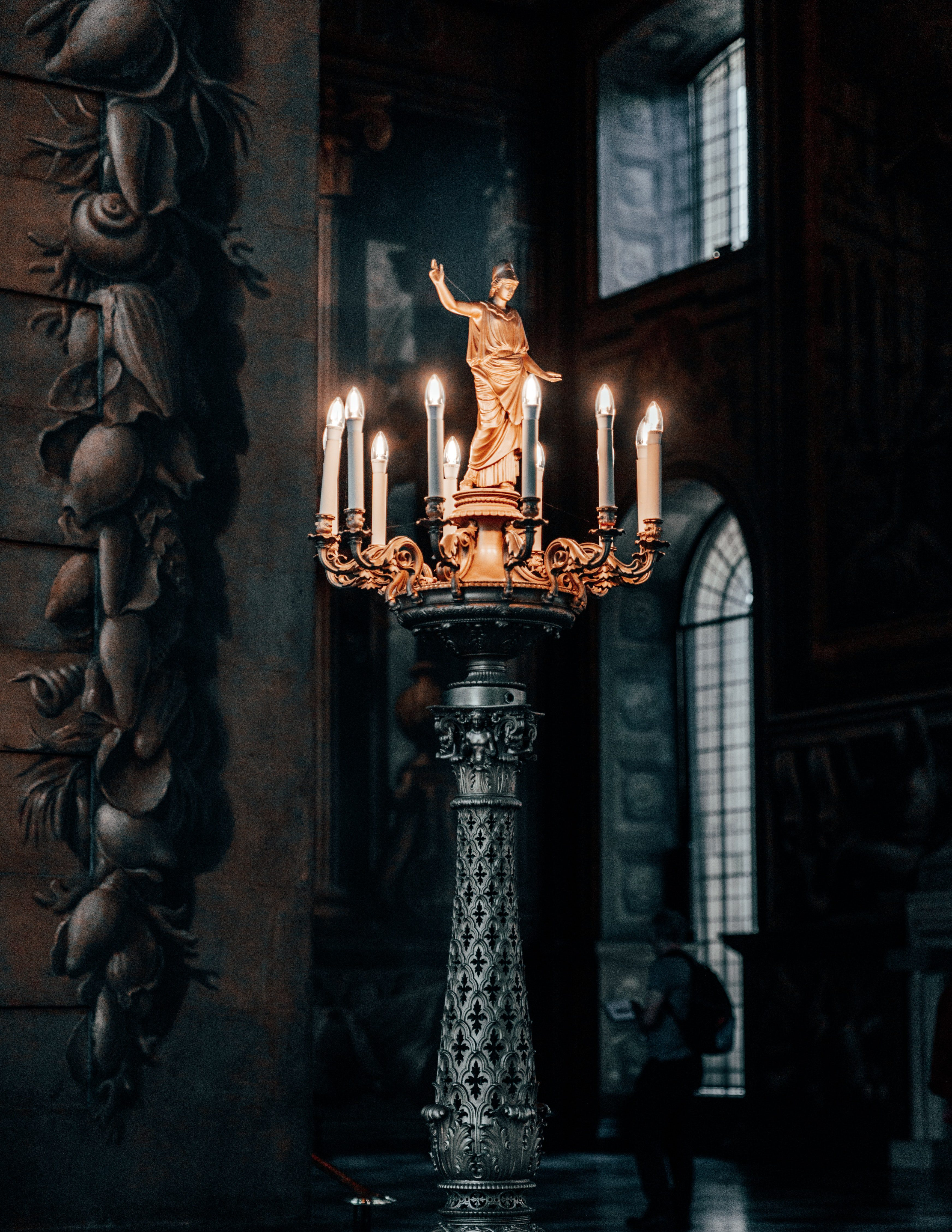 old church candles on candelabra with a saint statue on top